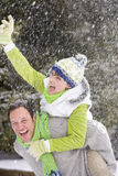 Man giving wife a piggyback in snowy woods Stock Photos