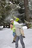 Man giving wife a piggyback in snowy woods Royalty Free Stock Photography