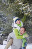 Man giving wife a piggyback in snowy woods Stock Photography