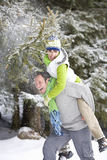 Man giving wife a piggyback in snowy woods Stock Photo