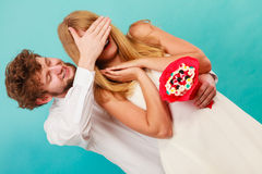 Man giving woman candy bunch covering her eyes. Stock Photos