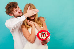 Man giving woman candy bunch covering her eyes. Stock Photography