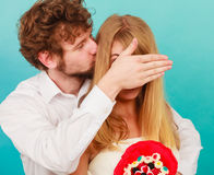 Man giving woman candy bunch covering her eyes. Royalty Free Stock Image