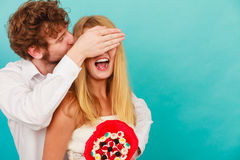 Man giving woman candy bunch covering her eyes. Stock Image