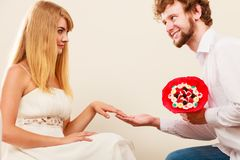Man giving woman candy bunch flowers. Happy couple. Handsome men giving pretty women candy bunch flowers. Young boyfriend with present gift kneeling in front of Royalty Free Stock Image