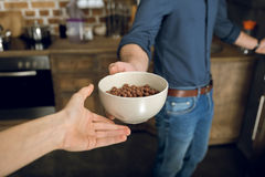 Man giving woman chocolate corn balls in bowl Stock Images