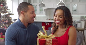 Man giving woman Christmas gift at home - she shakes package and tries to guess what's inside. Romantic Couple Exchanging Christmas Gifts Shot On R3D stock video