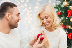 Man giving woman engagement ring for christmas. Love, couple, proposal, holidays and people concept - happy men giving diamond engagement ring in little red box royalty free stock photos