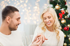 Man giving woman engagement ring for christmas. Love, couple, proposal, holidays and people concept - happy men giving diamond engagement ring to women over tree stock images