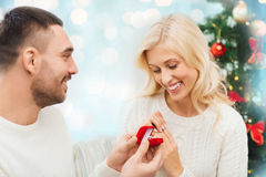 Man giving woman engagement ring for christmas. Love, christmas, couple, proposal and people concept - happy men giving diamond engagement ring in little red box royalty free stock photography
