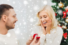 Man giving woman engagement ring for christmas Royalty Free Stock Images