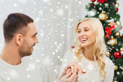 Man giving woman engagement ring for christmas Stock Photo
