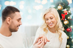 Man giving woman engagement ring for christmas. Love, christmas, couple, proposal and people concept - happy men giving diamond engagement ring to women over royalty free stock photography