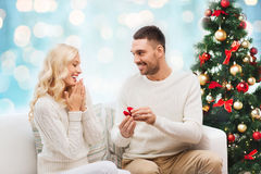 Man giving woman engagement ring for christmas. Love, christmas, couple, proposal and people concept - happy men giving engagement ring in little red box to royalty free stock images