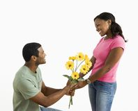 Man giving woman flowers. African American male giving pretty female a bouquet of yellow flowers Royalty Free Stock Images