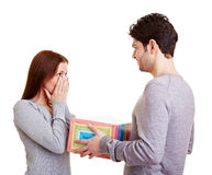 Man giving woman a gift. Man giving his surprised girlfriend a a gift Royalty Free Stock Photos