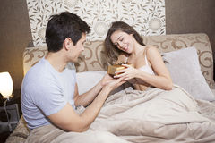 Man giving woman gift box in bed Stock Image