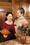 Man giving woman gifts. Caucasian man giving Caucasian woman card, present and flowers Royalty Free Stock Photo