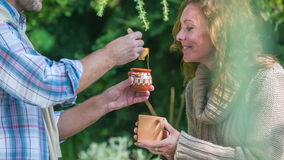 Man giving the woman a honey in to the cup of tea. Close up RAW footage of a men sweating the women tea with honey with wooden sponge in the middle of  a stock footage
