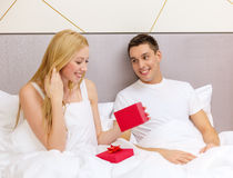 Man giving woman little red gift box Stock Images
