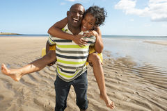 Man Giving Woman Piggyback Along Shoreline Stock Image