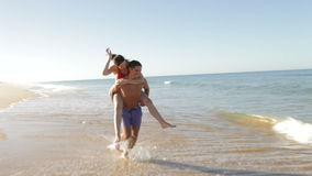 Man Giving Woman Piggyback As They Run Along Beach Stock Photography