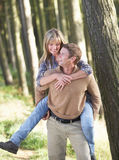 Man Giving Woman Piggyback On Country Walk Stock Photography