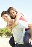 Man Giving Woman Piggyback In Park Royalty Free Stock Images
