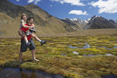 Man Giving Woman Piggyback Ride through Mountain Pond Stock Images