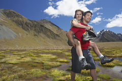 Man Giving Woman Piggyback Ride through Mountain Pond Stock Photo