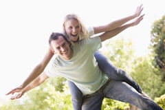 Man giving woman piggyback ride outdoors smiling Stock Image