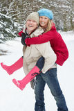 Man Giving Woman Piggyback In Snowy Woodland Royalty Free Stock Photos