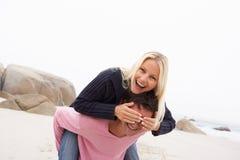 Man Giving Woman Piggyback On Winter Beach. Having Fun Stock Image