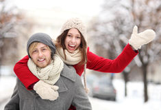 Man giving woman piggyback in winter setting stock images