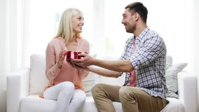 Man giving woman red heart shaped gift box. Relationships, love, people, valentines day and holidays concept - man giving woman red heart shaped gift box stock footage