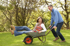 Man Giving Woman Ride In Wheelbarrow Royalty Free Stock Images