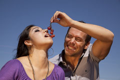 Man giving woman some grapes. A man is feeding a woman some red grapes in front of a blue sky Stock Photography
