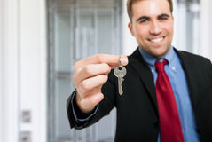 Home key. Man giving you a key Royalty Free Stock Image