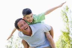 Man giving young boy piggyback ride smiling