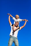 Man giving young boy piggyback ride smiling Royalty Free Stock Photos
