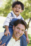 Man giving young boy shoulder ride smiling Stock Images