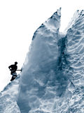 Man on glacier. Silhouette of a man using an ice pick while climbing a glacier Stock Image