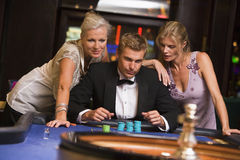 Man with glamorous women in casino. At roulette table Royalty Free Stock Photo