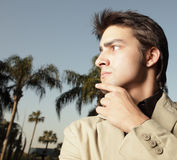 Man glancing away. Young businessman glancing away with his hand on his chin Royalty Free Stock Photography