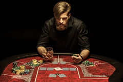 Man with glass of alcohol drink and poker chip in hands sitting at poker table Stock Images
