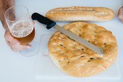 Man with a glass of beer, loaf of bread,  and knife on white tab Royalty Free Stock Images