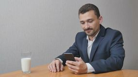 Man with a glass of milk engoys online. Man with a glass of milk and phone online. A businessman enjoys the Internet while drinking a healthy drink. A person Royalty Free Stock Photography