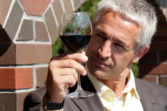 Man with glass of red wine. Mature man observing color in wine Stock Photos