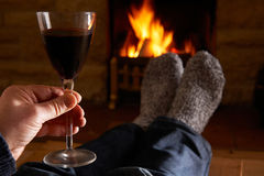 Man With Glass Of Red Wine Relaxing By Fire Stock Photo