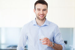 Man with glass of water. Man in kitchen with glass of water stock photography